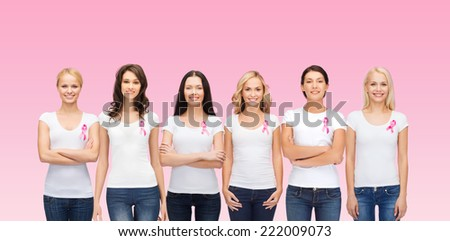 healthcare, people and medicine concept - group of smiling women in blank t-shirts with breast cancer awareness ribbons over pink background