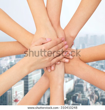 healthcare, people, gesture and medicine concept - close up of women hands on top of each other over city background