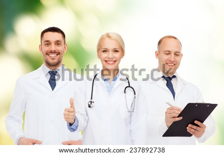 healthcare, people, gesture and medicine concept - group of doctors with stethoscope and clipboard showing thumbs up over green background - stock photo