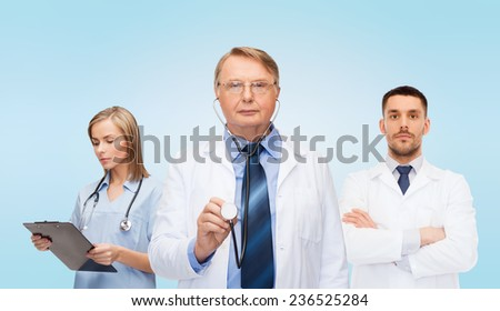 healthcare, profession and medicine concept - group of doctors in white coats with clipboard and stethoscopes over blue background - stock photo