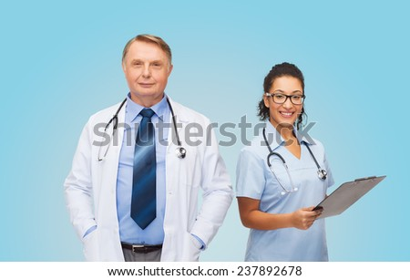 healthcare, profession and medicine concept - smiling doctors with clipboard and stethoscopes over blue background - stock photo