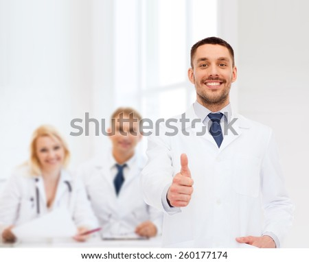 healthcare, profession and medicine concept - smiling male doctor showing thumbs up over white background - stock photo
