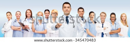healthcare, profession, gesture, people and medicine concept - international group of doctors with stethoscopes and clipboard pointing at you over gray background