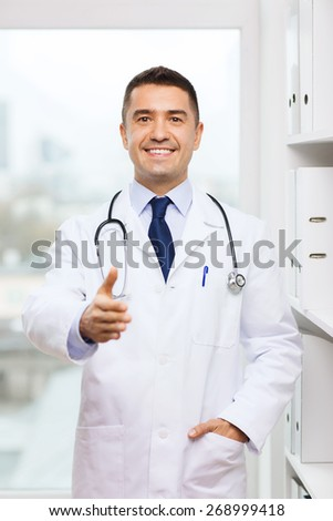 healthcare, profession, people and medicine concept - smiling male doctor in white coat giving his hand for handshake at medical office - stock photo