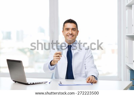healthcare, profession, people and medicine concept - smiling male doctor in white coat with tablets and laptop computer in medical office - stock photo