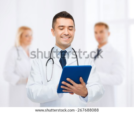 healthcare, profession, people and medicine concept - smiling male doctor in white coat with tablet pc over group of medics at hospital background