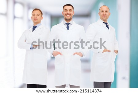 healthcare, profession, teamwork and medicine concept - smiling male doctors in white coats over hospital corridor background - stock photo