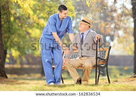 Healthcare professional during a conversation with senior man seated on wooden bench in a yard - stock photo