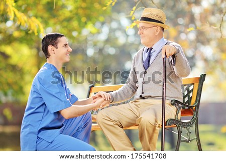 Healthcare professional helping senior man sitting on a bench outside - stock photo