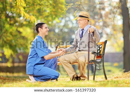 Healthcare professional helping senior man sitting on a wooden bench outside - stock photo