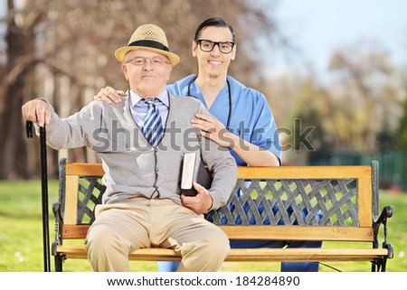 Healthcare professional posing with a senior man in park - stock photo