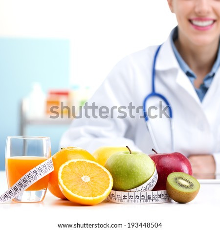 Healthcare professional promoting healthy eating, focus on fruit - stock photo