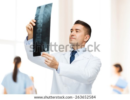 healthcare, roentgen, people and medicine concept - male doctor in white coat looking at x-ray over group of medics at hospital background - stock photo
