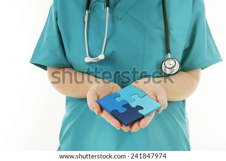 Healthcare Solutions - Nurse holding a completed Jigsaw Puzzle - stock photo