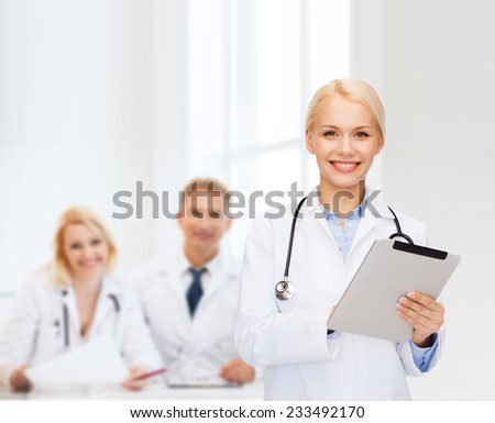 healthcare, technology and medicine concept - smiling female doctor with stethoscope and tablet pc computer - stock photo