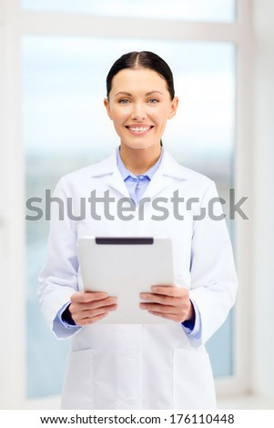 healthcare, technology and medicine concept - smiling young doctor with tablet pc computer in cabinet