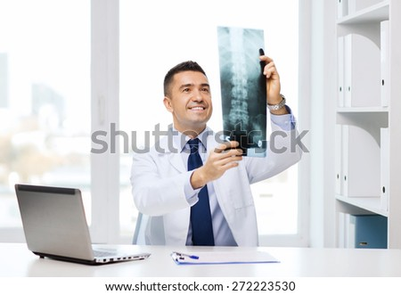 healthcare, technology, rontgen, people and medicine concept - smiling male doctor in white coat with laptop computer looking at x-ray in medical office - stock photo