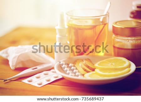 healthcare, traditional medicine and flu concept - tea cup with lemon, ginger, honey and pills on wooden table