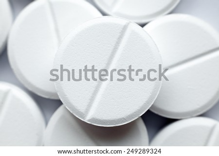 Healthcare, treatment, supplements. Close-up of white round pills on white background - stock photo