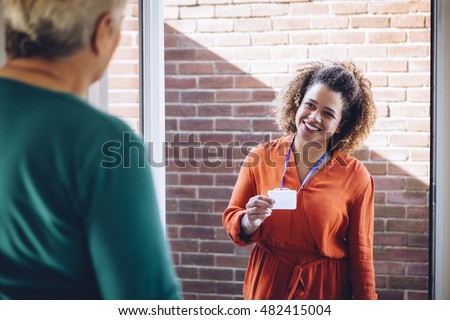 Healthcare worker showing her badge at the front door of a senior womans home.