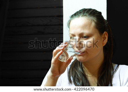 Healthiest drink - woman in the white shirt drinking fresh water on the dark grey background - stock photo