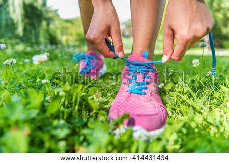 Healthy active lifestyle woman athlete tying running shoes. Happy sporty runner girl lacing shoelaces on pink fashion sneakers on summer grass in city park getting ready for a fitness morning jog. - stock photo
