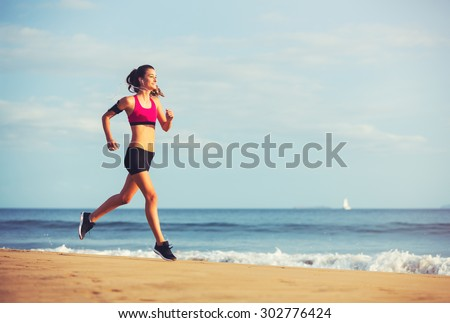 Healthy Active Lifestyle. Young sports fitness woman running on the beach at sunset.