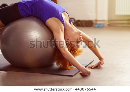 Healthy active young woman doing pilates in a gym lying back over the ball with her hands on the floor, close up side view with copy space - stock photo