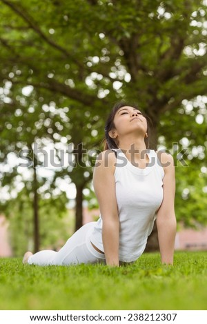 Healthy and beautiful young woman doing stretching exercises at park