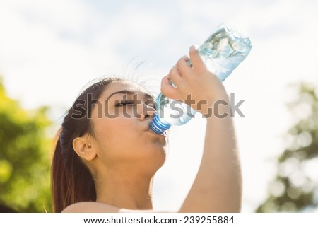 Healthy and beautiful young woman drinking water in park - stock photo
