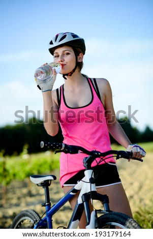 healthy and cheerful young woman riding bicycle outdoor in the countryside