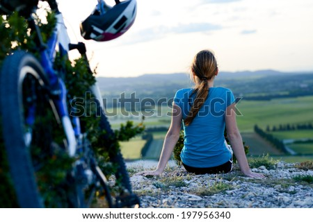 healthy and cheerful young woman riding mountain bike outdoor in the country - stock photo