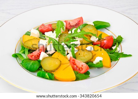 Healthy and Diet Food: Salad, Persimmon, Pickled Cucumber, Tomato, Arugula. Studio Photo