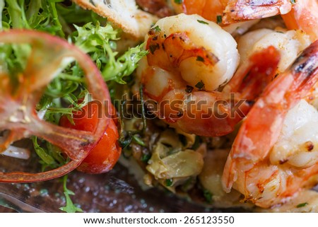 Healthy and fresh salad with shrimps and vegetables serving on the plate on a wooden table in a restaurant with decor