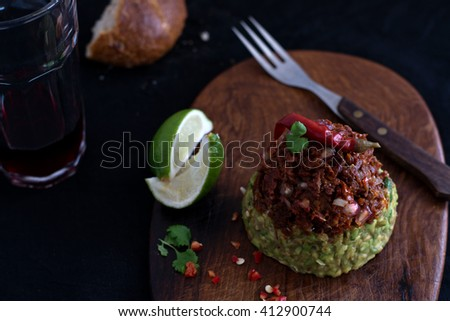 Healthy and fresh starter with avocado, sun-dried tomatoes, lime, chili, coriander and pomegranate seeds. Served on an oval, wood cutting board with wood fork.