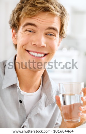 Healthy and happy young man holding glass of water while relaxing