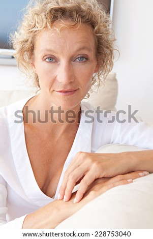 Healthy and successful mature professional woman sitting on a white sofa at home relaxing indoors, smiling with a flat tv screen in the background. Aspirational technology lifestyle and home living. - stock photo