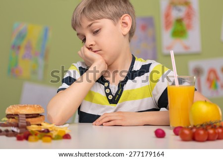 Healthy and unhealthy lunch on school desk - stock photo