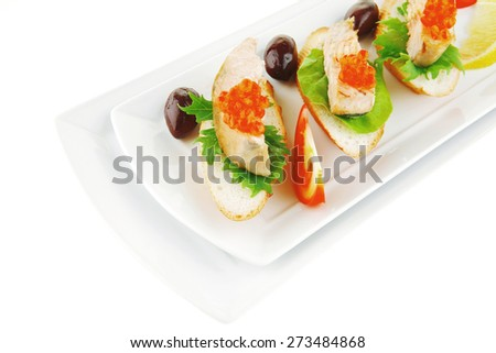 healthy appetizer : sandwich with sea salmon and red caviar, olives, tomato and lemon on white china plate isolated over white background - stock photo