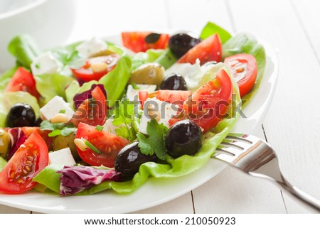 Healthy appetizing Mediterranean salad with fresh tomato, olives, feta cheese, herbs and lettuce, close up view on a plate