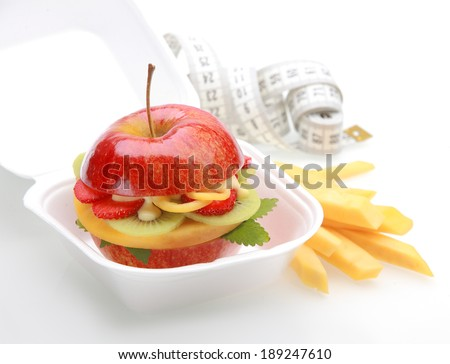 Healthy apple burger takeaway in a fast food container with a juicy red apple sliced through and filled with diced fresh tropical fruit and sauce with fruit batons or chips and a tape measure - stock photo