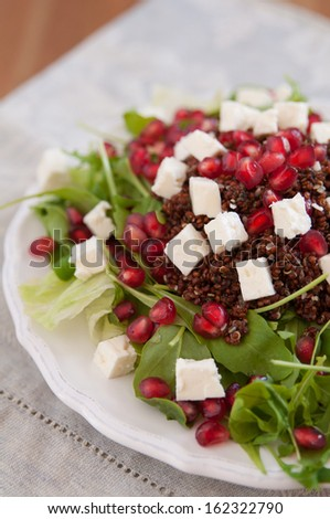 Healthy arugula salad with quinoa, feta cheese and pomegranate seeds - stock photo
