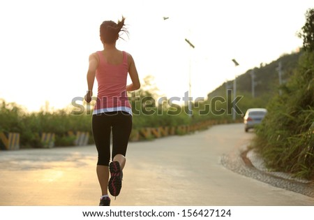 healthy asian woman runner running outdoor under sunrise - stock photo