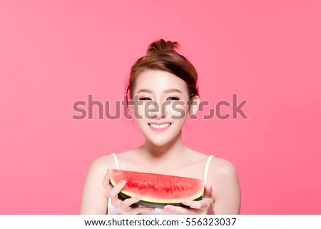 Healthy asian young woman eat watermelon, This girl really love fruits, She have beauty face and natural makeup, Isolated over pink background.