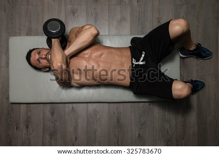 Healthy Athlete Exercising Triceps On Foor As Part Of Bodybuilding Training - stock photo