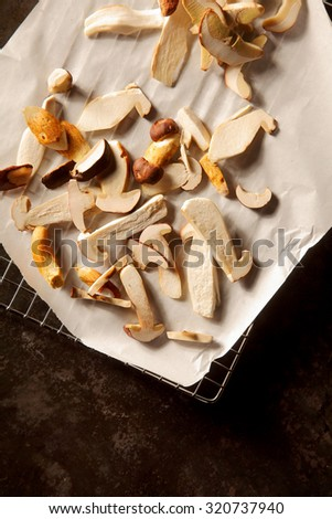 Healthy autumn harvest of sliced raw fresh forest mushrooms ready for use as a savory cooking ingredient on crumpled white paper over black, overhead view with copyspace - stock photo