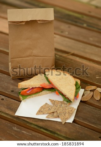 healthy back to school lunch with veggie sandwich and brown paper bag - stock photo