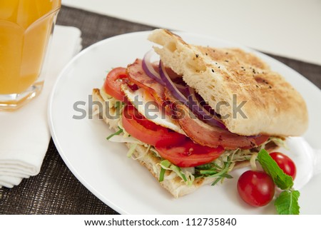Healthy bacon and egg burger with onions, tomatoes and lettuce on turkish bread. - stock photo