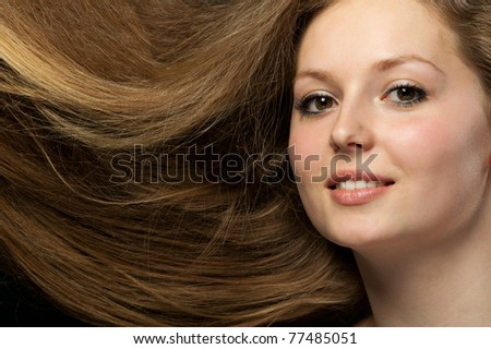 Healthy beautiful long hair closeup in motion created by wind. Portrait on black background