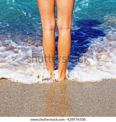 Healthy beautiful tan female legs on the sandy  sea beach  - stock photo